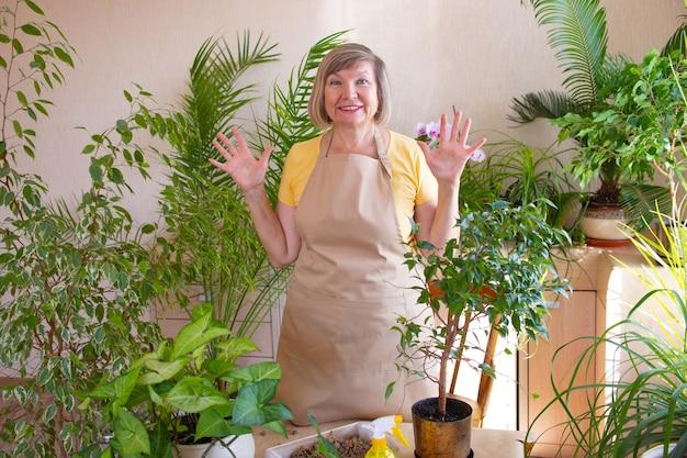 Glückliche gärtnerbloggerin zeigt klasse mit den händen und kümmert sich um pflanzen