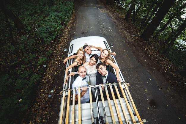 Glückliche gäste mit braut und bräutigam