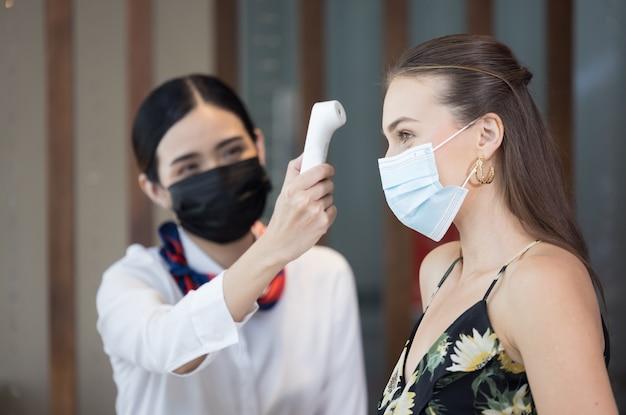 Glückliche gäste überprüfen das fieber mit einem digitalen thermometer auf scannen und schützen vor coronavirus covid-19 an der hotelrezeption