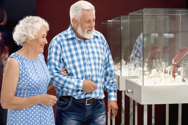 Glückliche gealterte paare, die schmuck im einkaufszentrum wählen