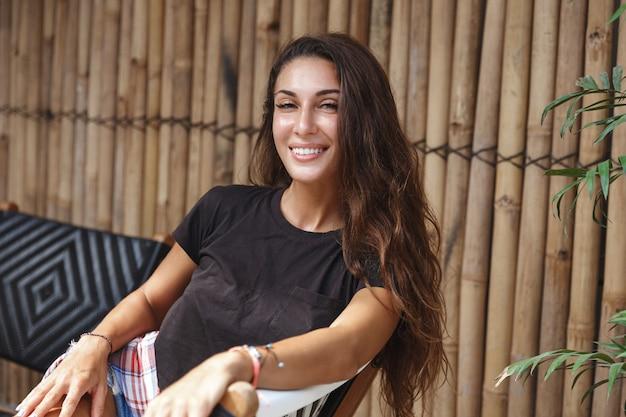 Glückliche gebräunte frau, die auf terrasse entspannt und in die kamera lächelt.