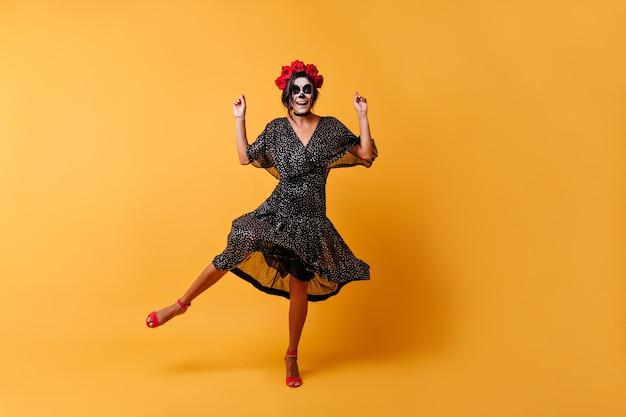 Glückliche gebräunte frau hat spaß beim tanzen im halloween-bild. in voller länge aufnahme eines mädchens im schwarzen outfit und mit rosen im haar