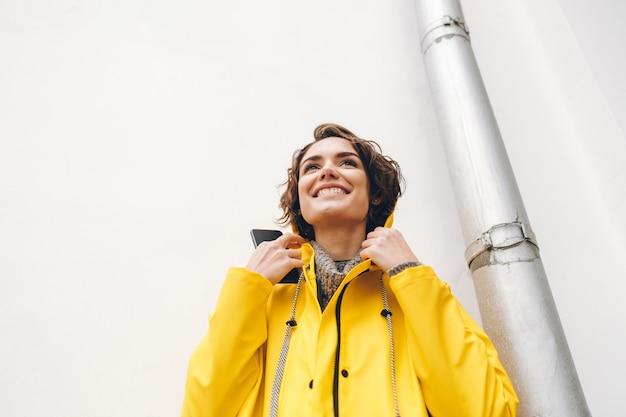 Glückliche gefühle der frau im gelben mantel, der vor der weißen wand hält den smartphone in der hand lächelt mit den perfekten zähnen steht
