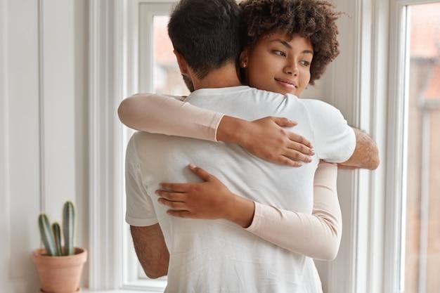 Glückliche gemischte paare umarmen sich, drücken unterstützung und liebe aus, haben freundschaftliche beziehungen, posieren in der nähe des fensters im wohnzimmer, genießen zusammengehörigkeit. vielfältiger freund und freundin umarmen sich drinnen