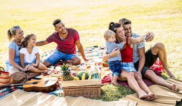 Glückliche gemischtrassige familien, die selfie auf pic nic gartenparty nehmen - multikulturelles freude- und liebeskonzept mit gemischten rassenleuten, die spaß zusammen picknickgrill vor sonnenuntergang haben