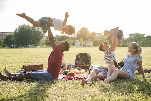 Glückliche gemischtrassige familien, die während der sommerferien im stadtpark picknick im freien machen - hauptaugenmerk auf dem rechten gesicht der frau