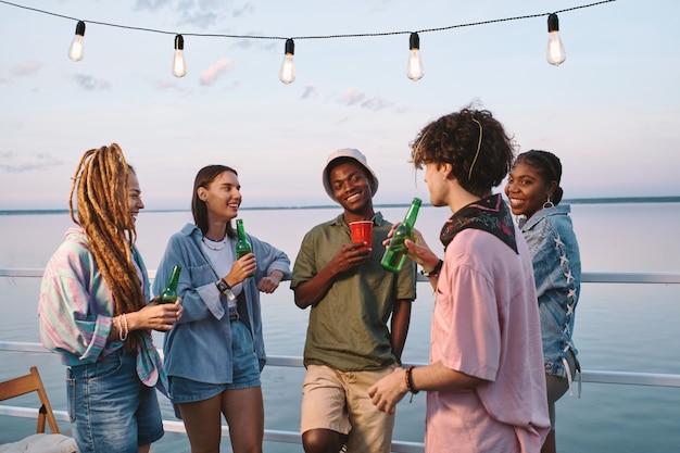 Glückliche gemischtrassige freunde mit getränken, die eine party im freien genießen