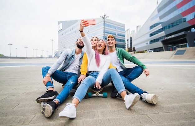 Glückliche gemischtrassige freundesgruppe, die selfie auf stadtstraße nimmt