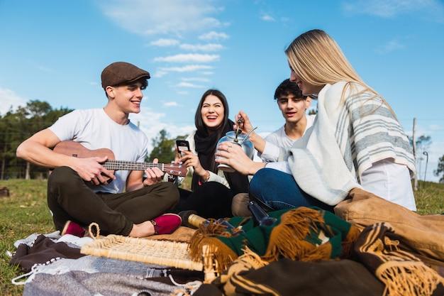 Glückliche gemischtrassige gruppe von freunden, die den tag genießen, der ukulele spielt und mate-tee auf dem land trinkt.
