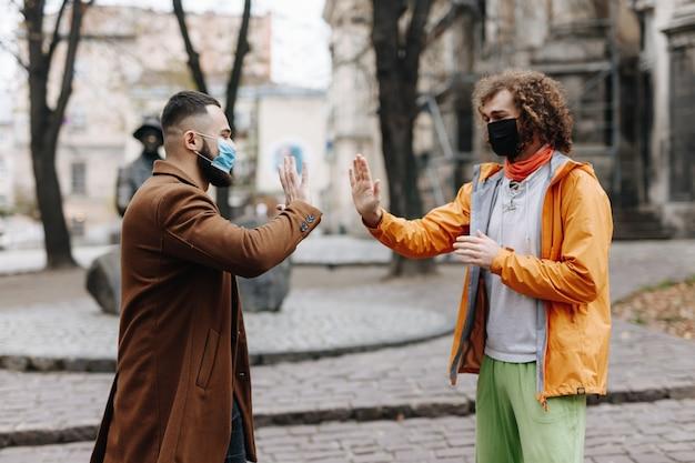 Glückliche gemischtrassige männer in freizeitkleidung, die auf der straße stehen und mit den händen grüßen. junge leute, die während der pandemie medizinische masken tragen.