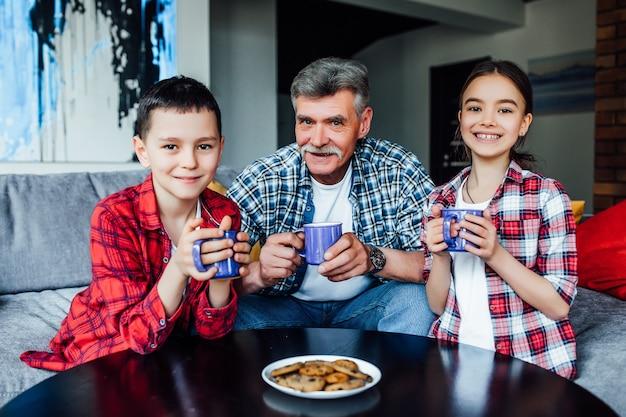 Glückliche generationen. fröhlicher lächelnder älterer mann, der tee trinkt, während er die zeit mit seinen enkeln genießt.