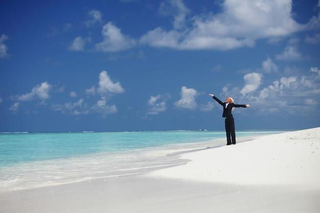 Glückliche geschäftsfrau an der einsamen ozeanküste