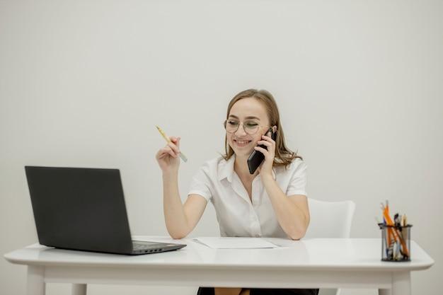 Glückliche geschäftsfrau, die am schreibtisch hinter ihrem laptop sitzt und spricht