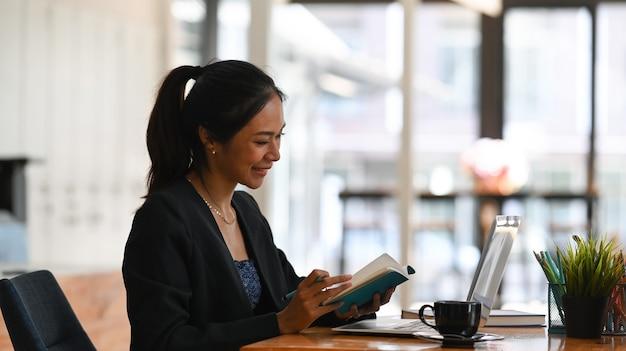 Glückliche geschäftsfrau, die an ihrem schreibtisch sitzt und auf dem schirm des laptop-computers schaut.
