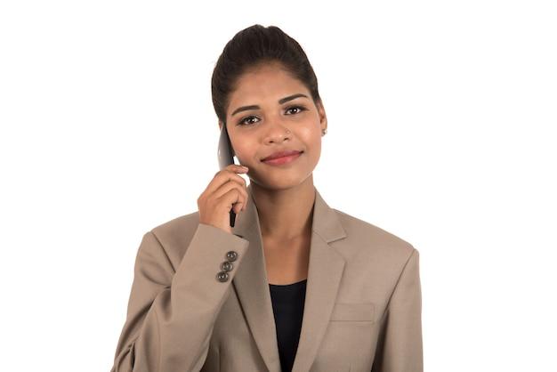 Glückliche geschäftsfrau, die auf dem handy oder smartphone lokalisiert auf weißem hintergrund spricht