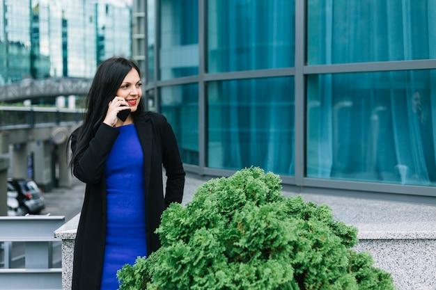 Glückliche geschäftsfrau, die auf mobiltelefon außerhalb des bürogebäudes spricht
