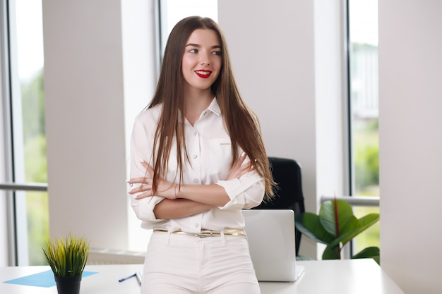 Glückliche geschäftsfrau, die auf schreibtisch im büro, büro europa lehnt