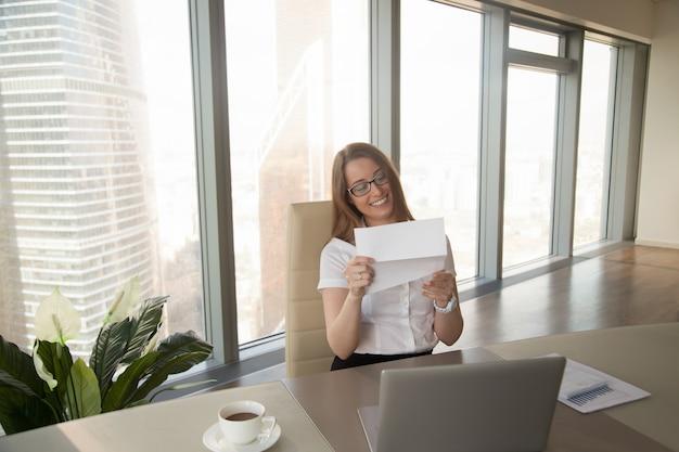 Glückliche geschäftsfrau, die geschäftsdokument, gute nachrichten im brief lesend hält