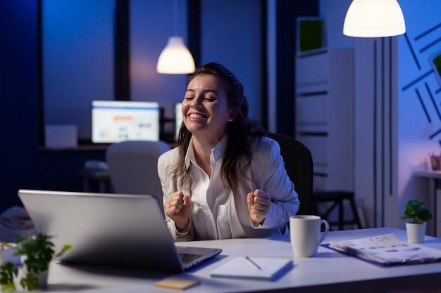 Glückliche geschäftsfrau, die großartige online-nachrichten auf dem laptop liest und an wirtschaftlichen möglichkeiten im büro des start-up-unternehmens arbeitet