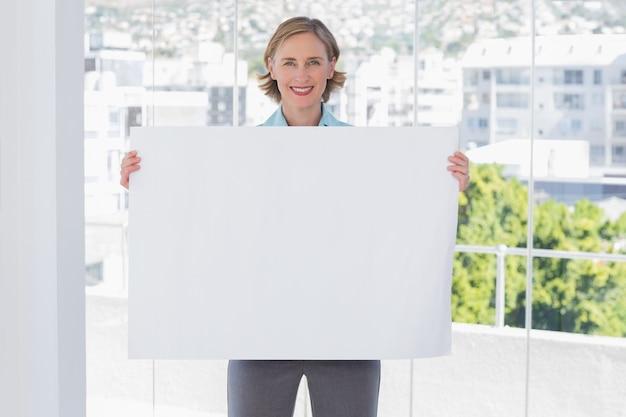 Glückliche geschäftsfrau, die großes weißes plakat hält