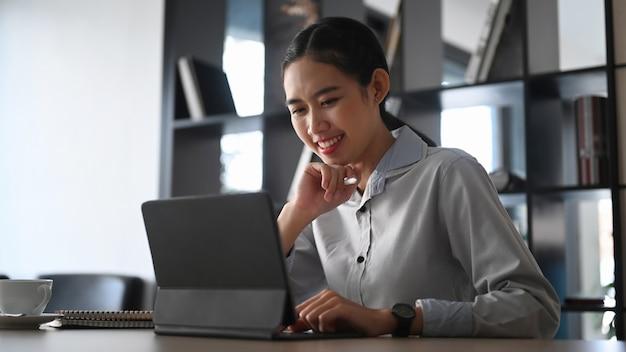 Glückliche geschäftsfrau, die gute nachrichten auf computertablette im büro lächelt und liest.