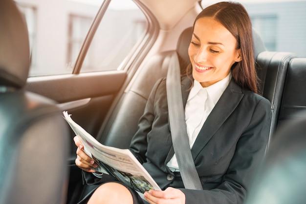 Glückliche geschäftsfrau, die innerhalb der autolesezeitung sitzt
