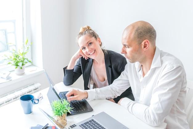Glückliche geschäftsfrau, die mit ihrem kollegen arbeitet an laptop sitzt