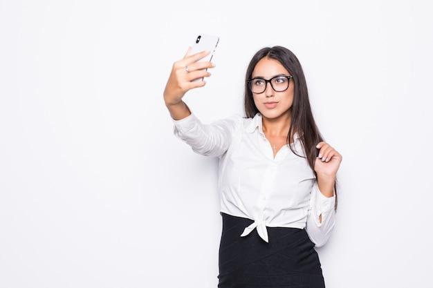 Glückliche geschäftsfrau, die selfie foto auf smartphone lokalisiert auf weiß nimmt