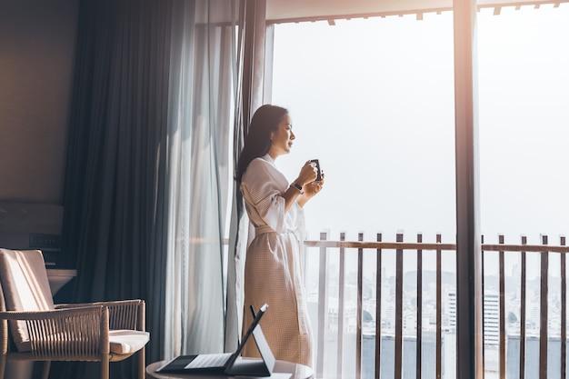 Glückliche geschäftsfrau im schlafrock steht nahe dem fenster, das tasse kaffee hält.