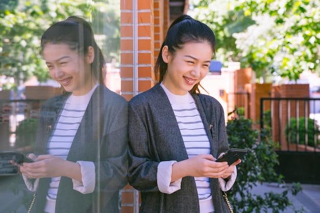 Glückliche geschäftsfrau in den straßen mit smartphone