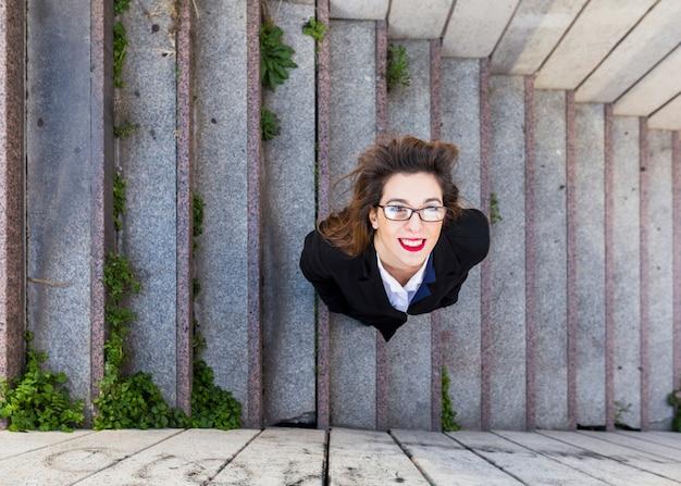 Glückliche geschäftsfrau in der klage, die draußen auf treppe steht