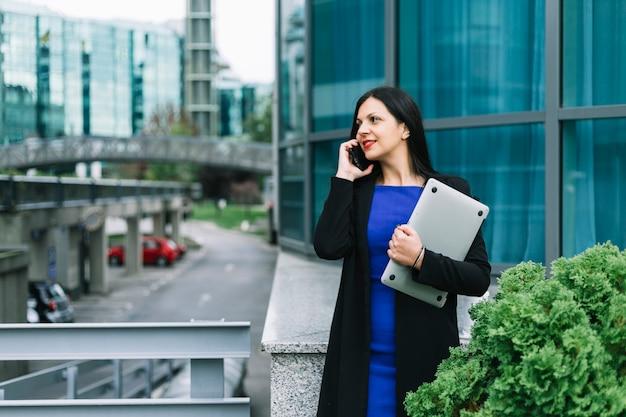 Glückliche geschäftsfrau mit laptop sprechend auf smartphone