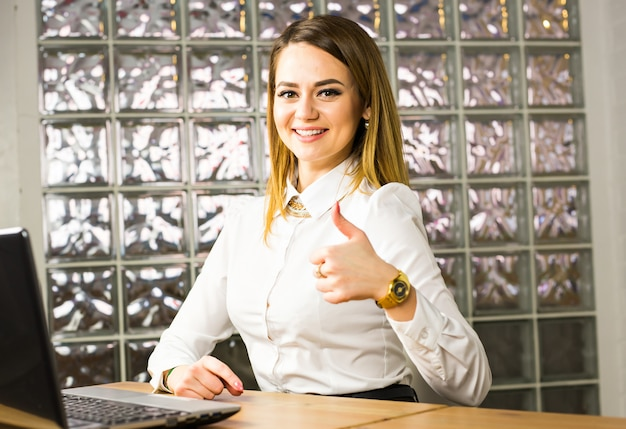 Glückliche geschäftsfrau mit laptop zeigt daumen hoch