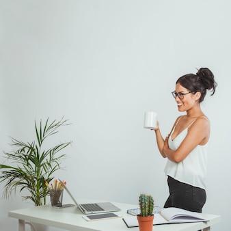 Glückliche geschäftsfrau posiert mit einem coffe mug im büro