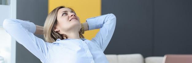 Glückliche geschäftsfrau sitzt an ihrem arbeitstisch und betrachtet kreative geschäftsideen der decke für ceiling