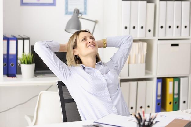 Glückliche geschäftsfrau sitzt an ihrem arbeitstisch und sucht nach erfolgreichem karriereaufbau in der wirtschaft
