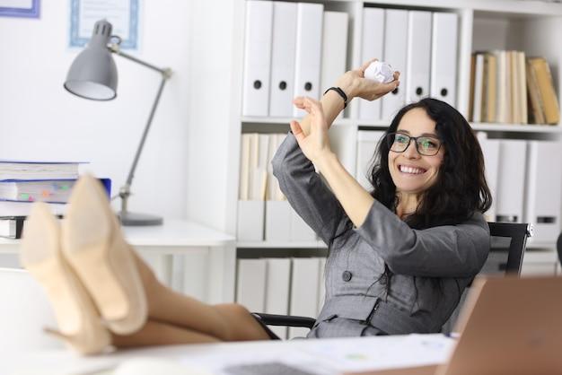 Glückliche geschäftsfrau sitzt an ihrem schreibtisch und wirft zerknittertes stück papier erfolgreiches geschäft