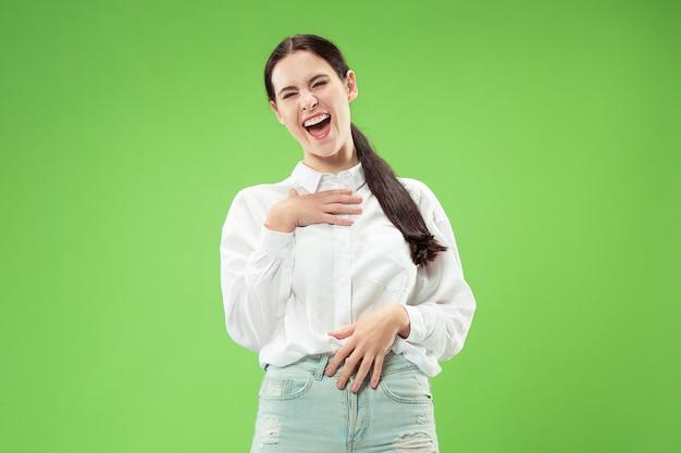 Glückliche geschäftsfrau stehend und lächelnd lokalisiert auf grüner studiowand