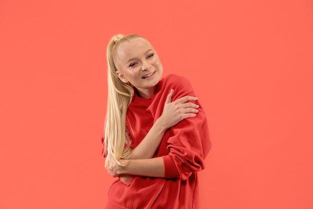 Glückliche geschäftsfrau stehend und lächelnd lokalisiert auf korallenstudio hintergrund. schönes weibliches halblanges porträt. junge emotionale frau. die menschlichen emotionen, gesichtsausdruck konzept