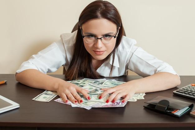 Glückliche geschäftsfrau umarmt viel geld