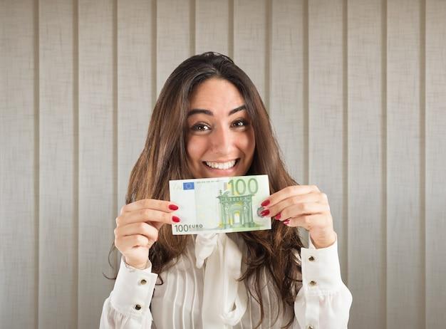 Glückliche geschäftsfrau zeigt eine 100-euro-banknote
