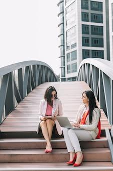 Glückliche geschäftsfrau zwei, die auf treppenhaus mit tagebuch und laptop sitzt