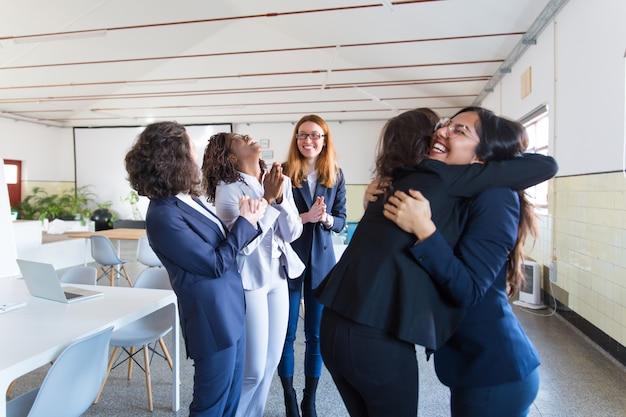 Glückliche geschäftsfrauen, die im büro sich treffen