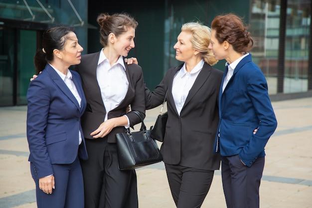 Glückliche geschäftsfrauen feiern teamerfolg, stehen draußen, umarmen und sprechen. teamunterstützung und glückwunschkonzept