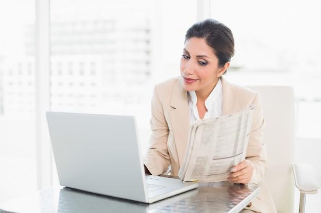 Glückliche geschäftsfraulesezeitung beim arbeiten an laptop