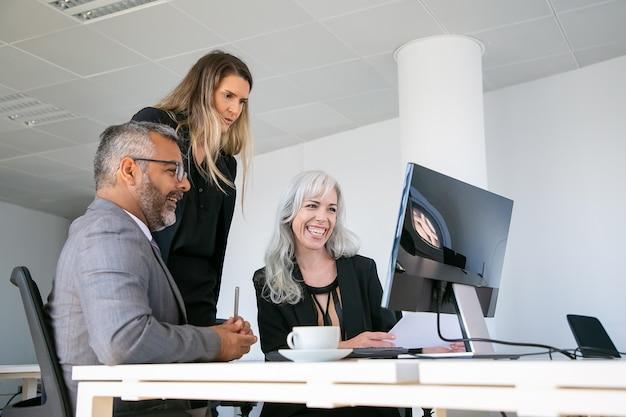 Glückliche geschäftsgruppe, die präsentation beobachtet und lacht. profis sitzen zusammen am arbeitsplatz, schauen auf den computermonitor und lachen. geschäftskommunikations- oder teamwork-konzept
