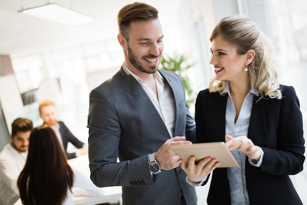 Glückliche geschäftskollegen im modernen büro mit tablet
