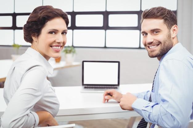 Glückliche geschäftsleute, die am laptopschreibtisch sitzen