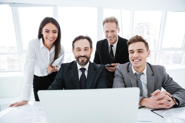 Glückliche geschäftsleute, die am tisch sitzen, betrachten laptop-computer im büro. vorderansicht