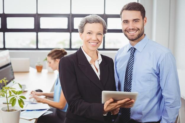 Glückliche geschäftsleute, die digitale tablette im büro verwenden